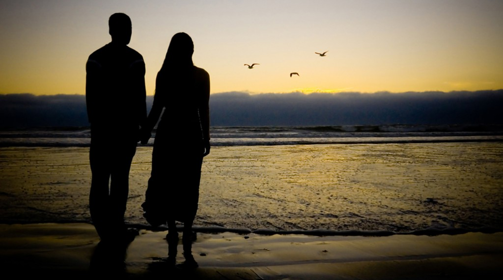 A couple watching sunset on the beach. Couples Counselling can assist when the joys of initial romance fade.
